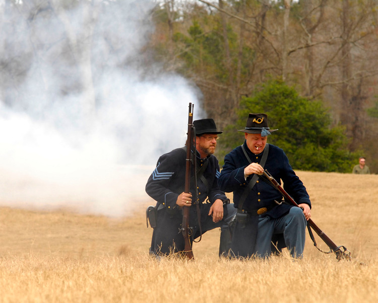 Two Union infantry reenactors kneel on the field during the battle. The Skirmish at Gamble's Hotel happened on March 5, 1885 when 500 federal soldiers, under the command of Reuben Williams of the 12th Indiana Infantry, marched into Florence to destroy the railroad depot but were met by Confederate soldiers backed up with 400 militia. The reenactment, held by the 23rd South Carolina Infantry, was held at the Rankin Plantation in Florence, South Carolina on Saturday, March 5, 2011. Photo Copyright 2011 Jason Barnette