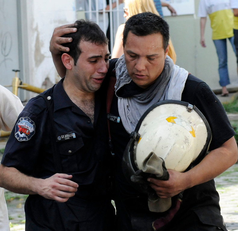 . Picture released by Noticias Argentinas showing a fireman comforting a co-worker during a fire at a warehouse in Barracas, in southern Buenos Aires, on February 5, 2014.  AFP PHOTO / NA / Hugo Villalobos   /AFP/Getty Images