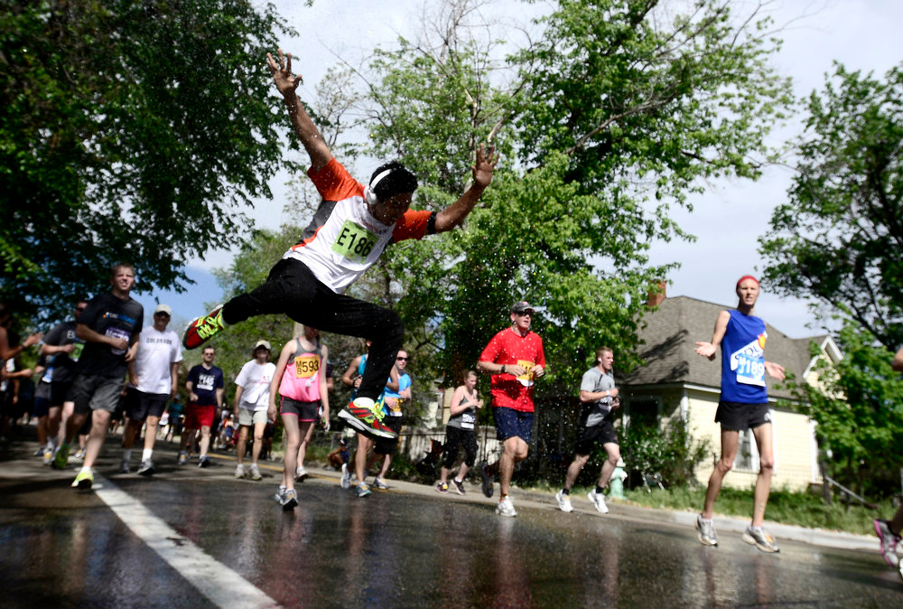 . Tashi Sherpa leaps into the air while being sprayed with water during the Bolder Boulder in Boulder, Colorado May 27, 2014.  DAILY CAMERA/ Mark Leffingwell