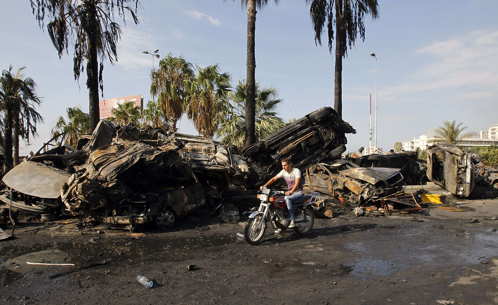 . A man on a motorcycle drives past the site of a blast outside the Al-Taqwa mosque in the northern city of Tripoli on August 23, 2013.  AFP PHOTO/ANWAR  AMRO/AFP/Getty Images