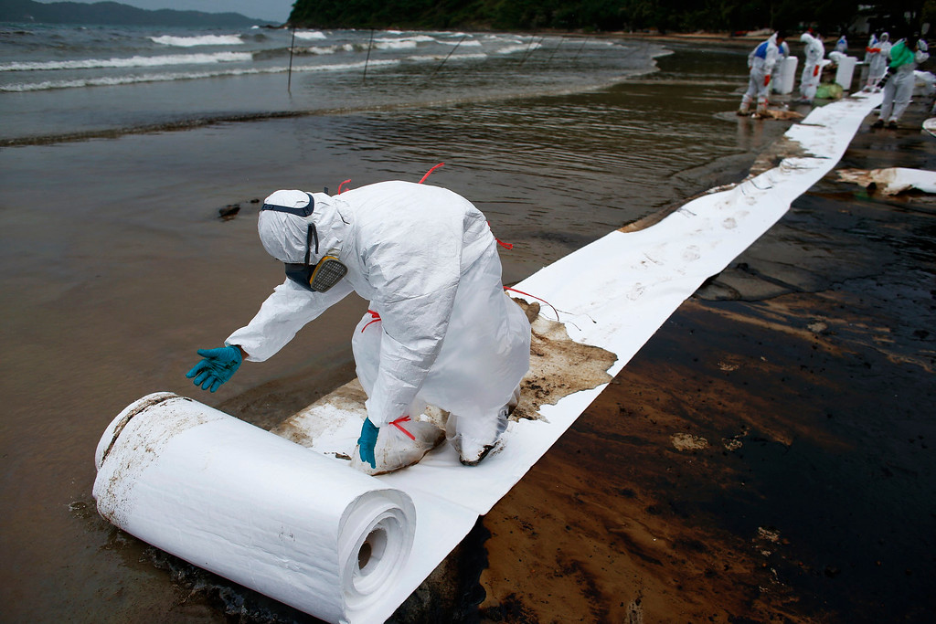 . A Thai soldier in white biohazard suit rolls out a ream of special paper in a clean-up operation at Ao Prao Beach on Koh Samet, Rayong July 30, 2013. Crude oil that leaked from a pipeline in the Gulf of Thailand over the weekend has reached a Thai tourist resort, pipeline operator PTT Global Chemical Pcl said on Monday. Around 50,000 liters of crude oil poured into the sea on Saturday around 20 km (12 miles) off the coast of Rayong, southeast of the capital Bangkok. REUTERS/Athit Perawongmetha