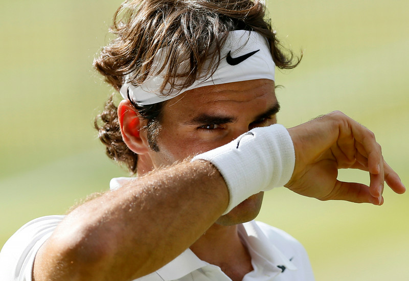 . Roger Federer of Switzerland wipes his face during  the men\'s singles semifinal match against Milos Raonic of Canada at the All England Lawn Tennis Championships in Wimbledon, London, Friday, July 4, 2014. (AP Photo/Ben Curtis)