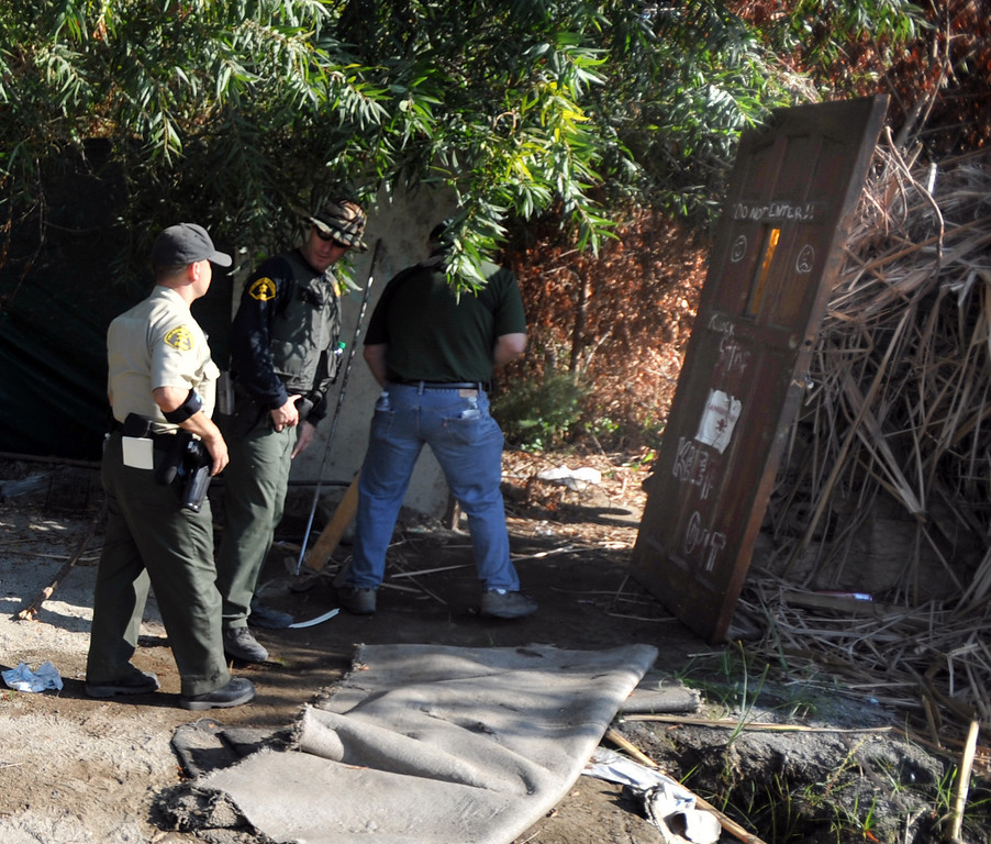 . Los Angeles County Sheriff\'s Deputies search a homeless camp in the river bed area of the San Gabriel River near South El Monte on Thursday September 12, 2013. (Whittier Daily News/Staff Photo by Keith Durflinger)