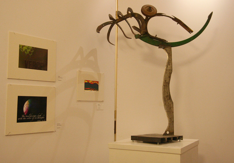 Brad Lail's metal sculpture frames the graphic design works of Ashleigh Blue, as well as a drawing by Cam Mitchell.