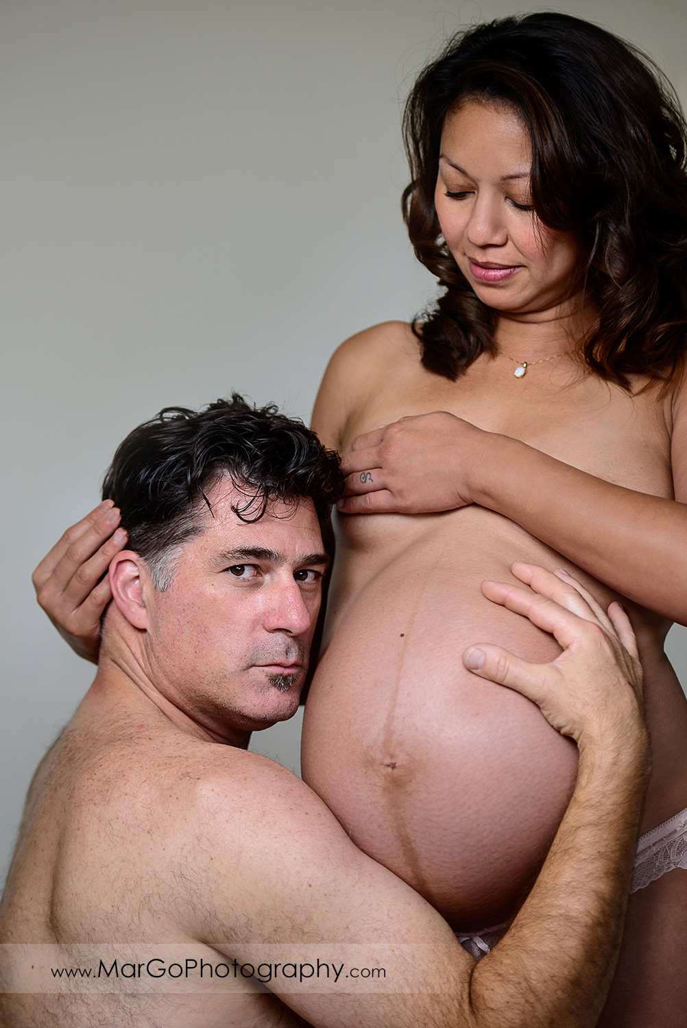 naked man holding pregnant woman belly and looking into camera