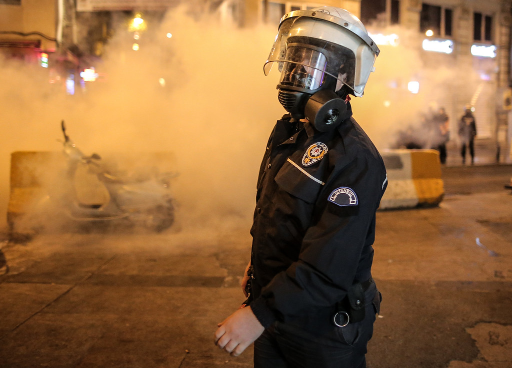 . Turkish riot police officer stands while police use water cannons and tear gas to disperse people who were protesting against Turkey\'s policy in Syria as fighting intensified between Syrian Kurds and the militants of Islamic State group in Kobani, Syria, in Istanbul, Turkey, late Tuesday, Oct. 7, 2014. Kurdish protesters clashed with police in Turkey leaving at least a dozen people dead and scores injured Tuesday. (AP Photo/Emrah Gurel)
