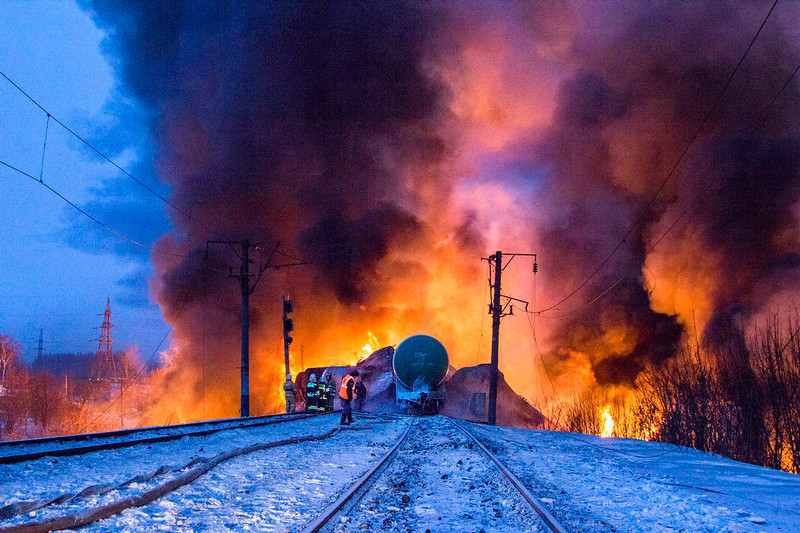 . In this photo provided by the Ministry of Emergency Situations Kirov Branch press service, firefighters and emergency ministry employees watch burning tankers early Wednesday, Feb. 5, 2014, near Posdino in Kirov region of Russia, some 800 km ( about 500 miles) northeast of Moscow. 32 tankers were derailed and 12 of them burned. No casualties were reported. (AP Photo/ Ministry of Emergency Situations, Kirov Branch Press Service)