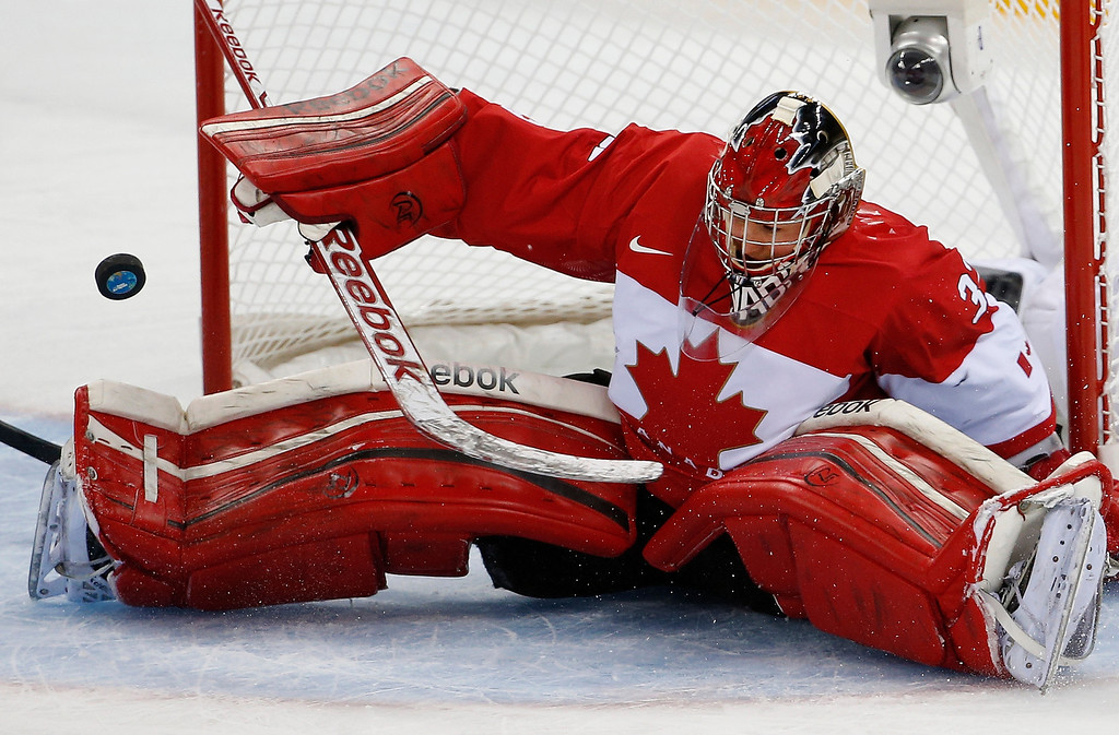 . Goalkeeper Charline Labonte of Canada bats the the puck away during the 2014 Winter Olympics women\'s ice hockey game against the United States at Shayba Arena, Wednesday, Feb. 12, 2014, in Sochi, Russia. (AP Photo/Petr David Josek)