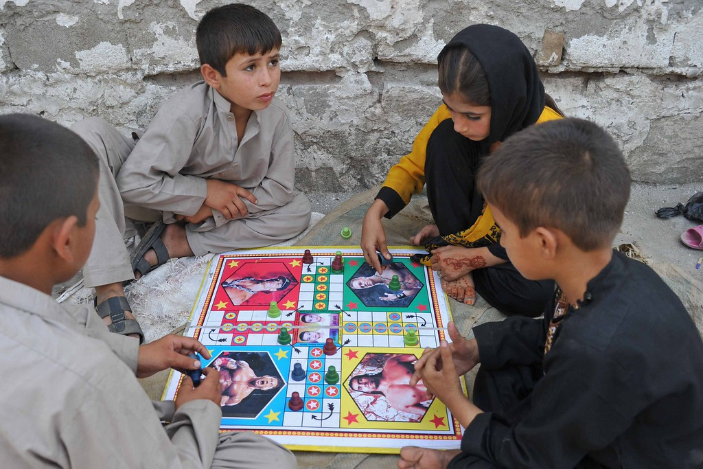 . Afghan children play a Ludo board game,  a board adorned with portraits of sports entertainment wrestlers, as they celebrate the second day of Eid al-Adha on the outskirts of Jalalabad on October 16,2013.  AFP PHOTO/ Noorullah  Shirzada/AFP/Getty Images