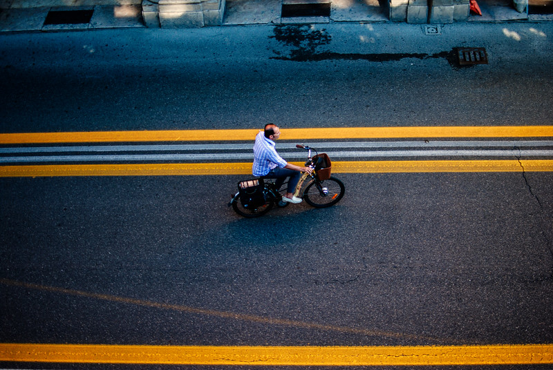 looking down on man riding bike yellow lines bologna italy morning - Copy.jpg