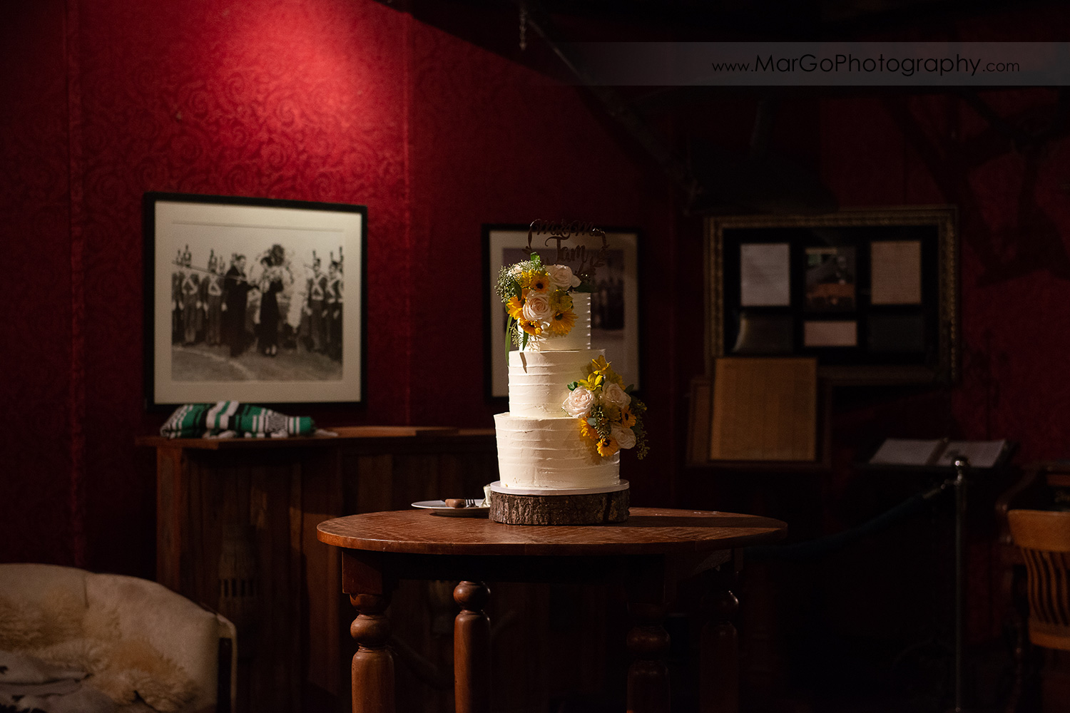 wedding cake decorated with yellow flowers in red room at Long Branch Saloon & Farms in Half Moon Bay