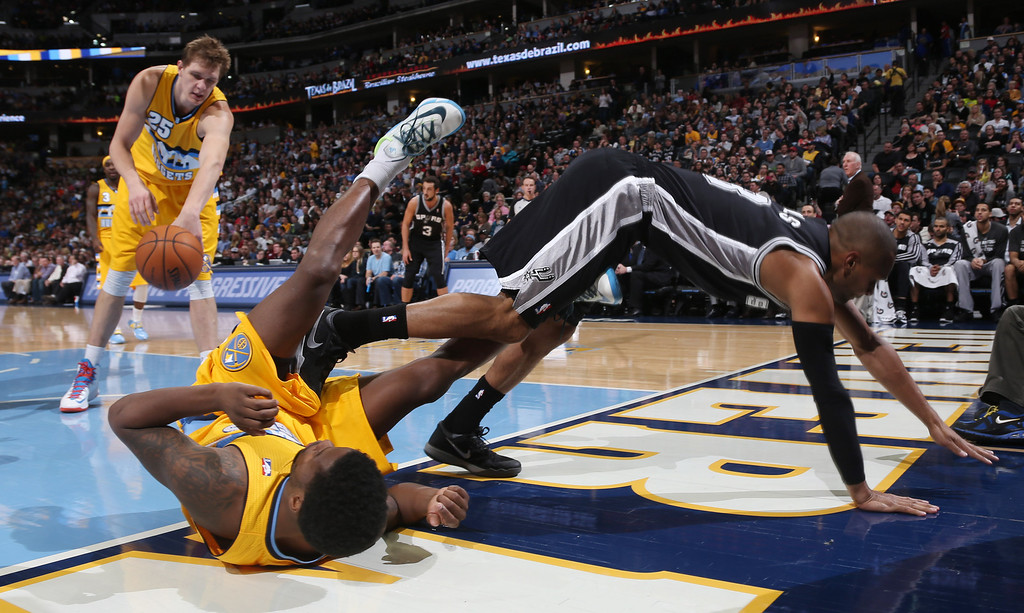 . Denver Nuggets guard Aaron Brooks, front left, is bowled over by San Antonio Spurs guard Patty Mills, front right, of Australia, as Nuggets center Timofey Mozgov, back, of Russia, picks up the ball in the third quarter of the Spurs\' 133-102 victory in an NBA basketball game in Denver, Friday, March 28, 2014. Mills was called for an offensive foul on the play. (AP Photo/David Zalubowski)