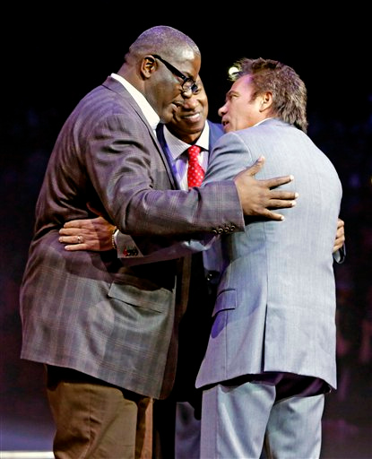 . Detroit Pistons owner Tom Gores, right, greets Joe Dumars, left, president of basketball operations, and former Piston Isiah Thomas during a half-time celebration of their 1989 NBA championship at an NBA basketball game Friday, March 28, 2014, in Auburn Hills, Mich. (AP Photo/Duane Burleson)