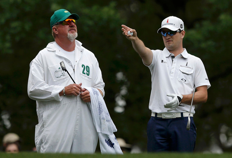 . Zach Johnson of the U.S. (R) talks to his caddie Damon Green before hitting his tee shot on the fourth hole during final round play in the 2013 Masters golf tournament at the Augusta National Golf Club in Augusta, Georgia, April 14, 2013.  REUTERS/Phil Noble