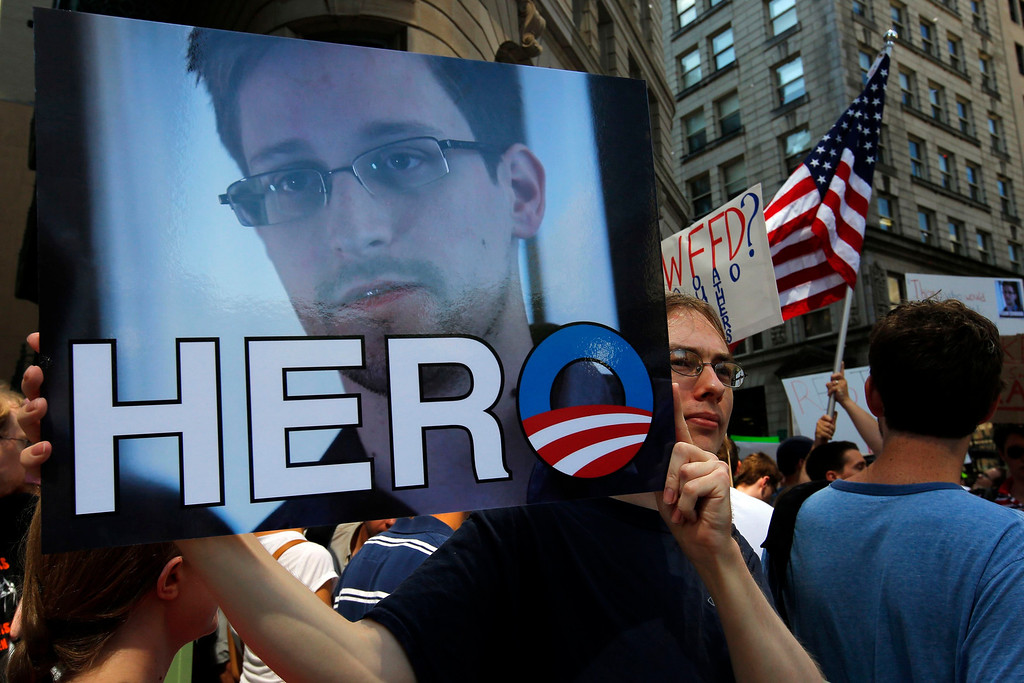 ". A demonstrator holds a sign with a photograph of former U.S. spy agency NSA contractor Edward Snowden and the word ""HERO\"" during Fourth of July Independence Day celebrations in Boston, Massachusetts July 4, 2013. People across the United States gathered on Thursday for parades, picnics and fireworks at Independence Day celebrations, held under unprecedented security following the Boston Marathon bombings. Spectators waving U.S. flags and wearing red, white and blue headed for public gatherings in Boston, New York, Washington, Atlanta and other cities under the close watch of police armed with hand-held chemical detectors, radiation scanners and camera surveillance, precautions sparked by the deadly April 15 bombings.     REUTERS/Brian Snyder"