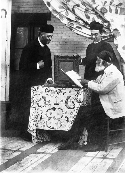 Two Los Angeles Plaza church priests with Don Antonio Coronel examining church records, ca.1885-1900