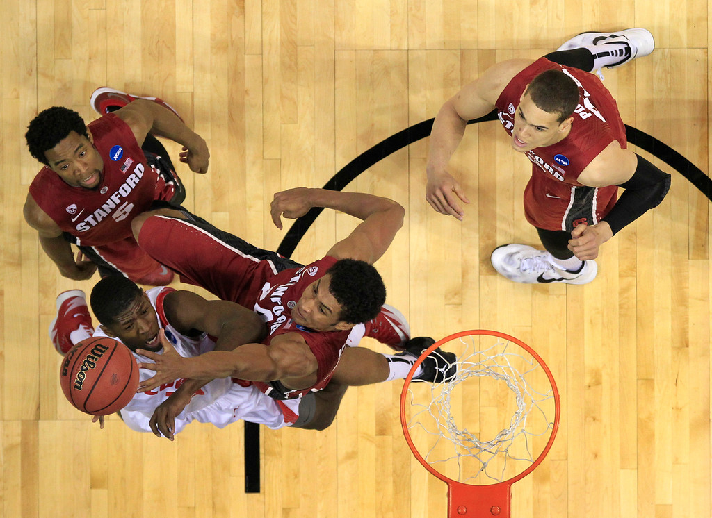 . Stanford\'s Josh Huestis rejects a shot from New Mexico\'s Deshawn Delaney, bottom, left, as Stanford\'s Chasson Randle, top left, and Dwight Powell, top right, watch during the first half of a second-round game in the NCAA college basketball tournament Friday, March 21, 2014, in St. Louis. (AP Photo/Jeff Roberson)
