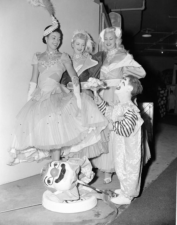 . With a princely gesture, circus midget Prince Paul presents flowers to three English girls who are in the show, backstage during the New York run, April 14, 1953. The girls are: left to right, Pat Cooper, who is from Devonshire; Shiley Coomas and Brinda Elliot, both of London. (AP Photo/VN)