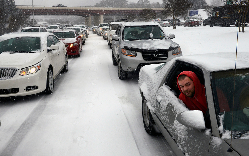 . Kevin Miller looks out of the passenger window of his friend\'s car as they sit in stuck traffic during a winter storm Wednesday Feb. 12, 2014, in Raleigh, N.C. (AP Photo/The News & Observer, Scott Sharpe)