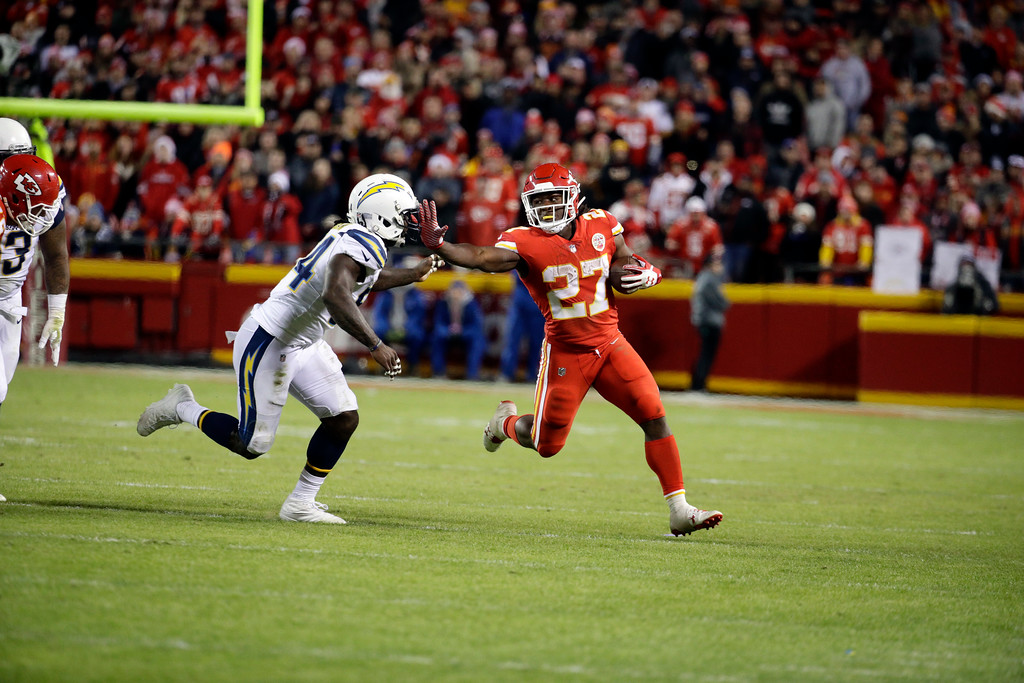 . Kansas City Chiefs running back Kareem Hunt (27) runs away from Los Angeles Chargers linebacker Melvin Ingram (54) during the second half of an NFL football game in Kansas City, Mo., Saturday, Dec. 16, 2017. (AP Photo/Charlie Riedel)