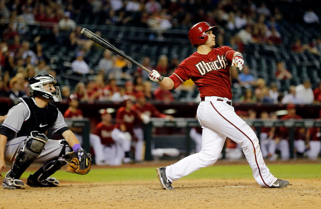 . Arizona Diamondbacks\' Miguel Montero watches his walk off solo home run take flight as Colorado Rockies catcher Jordan Pacheco watches during the 10th inning of a baseball game on Wednesday, April 30, 2014, in Phoenix. The Diamondbacks won 5-4. (AP Photo/Matt York)