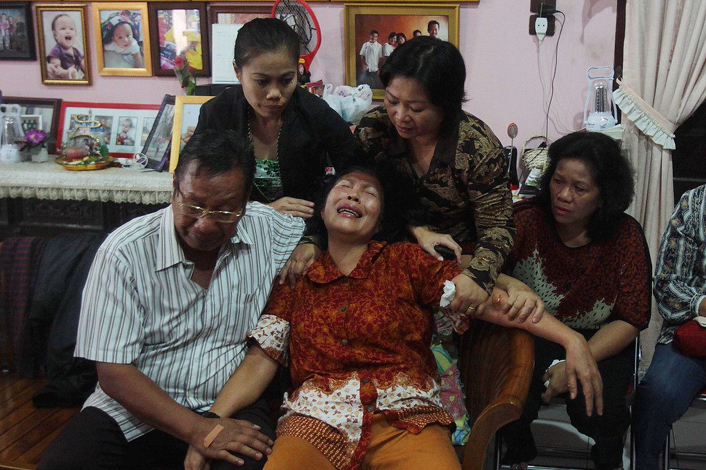 . Risman Siregar (L) comforts his wife Erlina Panjaitan (C), parents of Firman Chandra Siregar, a 24 year-old passenger of Malaysia Airlines flight 370 that went missing on March 8, in Medan on March 9, 2014.  Malaysia is investigating four names on the flight manifest of the airliner with 239 people aboard that vanished, as it probes a possible terror link, the Transport Minister Hishammuddin Hussein said.    AFP PHOTO / ATARATAR/AFP/Getty Images
