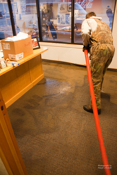 Chris Andrson vaccumes up water at the Bear Paw Credit Union from a broken water line