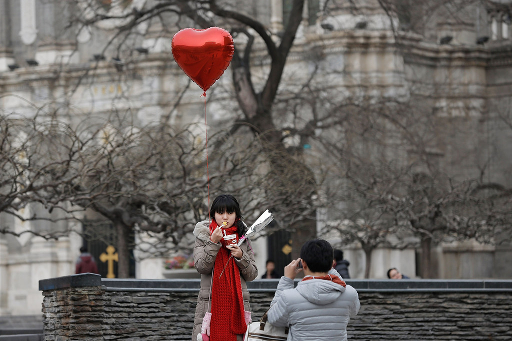 . A woman holding a heart balloon poses for a photo during on Valentine\'s Day February 14, 2013 in Beijing, China. Young Chinese couples have embraced the Western concept of Valentine\'s Day with hawkers selling roses and chocolates.  (Photo by Lintao Zhang/Getty Images)