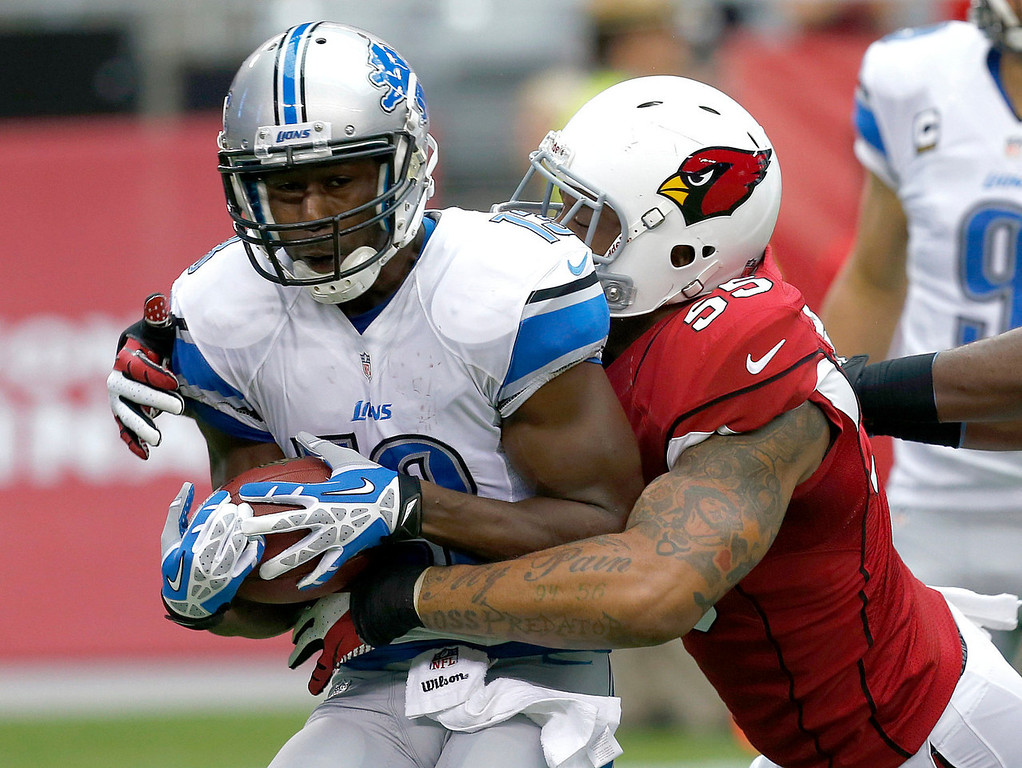 . Detroit Lions wide receiver Nate Burleson is tackled by Arizona Cardinals defensive end John Abraham (55) during the first half of a NFL football game, Sunday, Sept. 15, 2013, in Glendale, Ariz. (AP Photo/Ross D. Franklin)