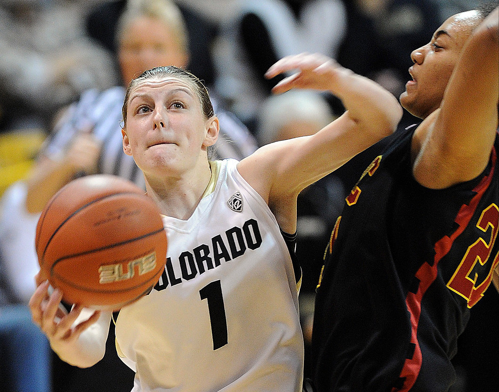 . Lexy Kresl of Colorado drives on Alexyz Vaioletama of USC   during the first half of the March 2, 2014 game in Boulder, Colo. (Class Grassmick/Daily Camera)