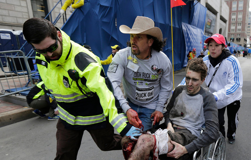 . Medical responders run an injured man past the finish line the 2013 Boston Marathon following an explosion in Boston, Monday, April 15, 2013. Two explosions shattered the euphoria of the Boston Marathon finish line on Monday, sending authorities out on the course to carry off the injured while the stragglers were rerouted away from the smoking site of the blasts. (AP Photo/Charles Krupa)
