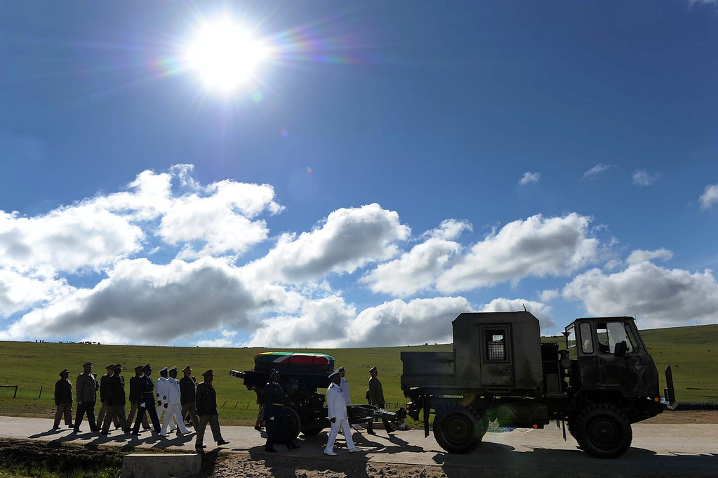 . The casket of Nelson Mandela is brought in a military parade on a gun carriage from the family home to the funeral tent, prior to his burial, in Qunu, South Africa Sunday, Dec. 15, 2013.  (AP Photo/Elmond Jiyane, GCIS)