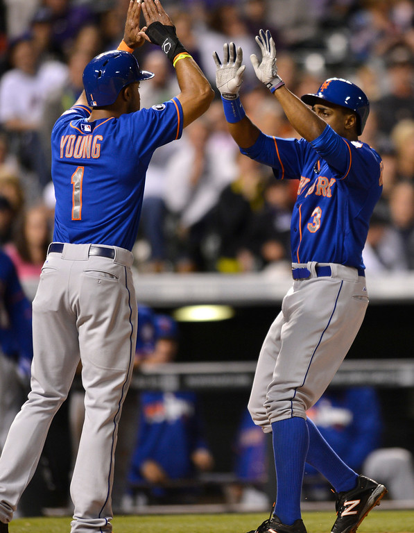 . New York Mets\' Curtis Granderson (3) is congratulated by teammate Chris Young (1) after a two-run homer against the Colorado Rockies during the sixth inning of a baseball game, Friday, May 2, 2014, in Denver. (AP Photo/Jack Dempsey)