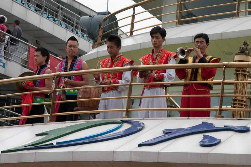 Bai guys play music to welcome tourists as they embark the cruise ship.