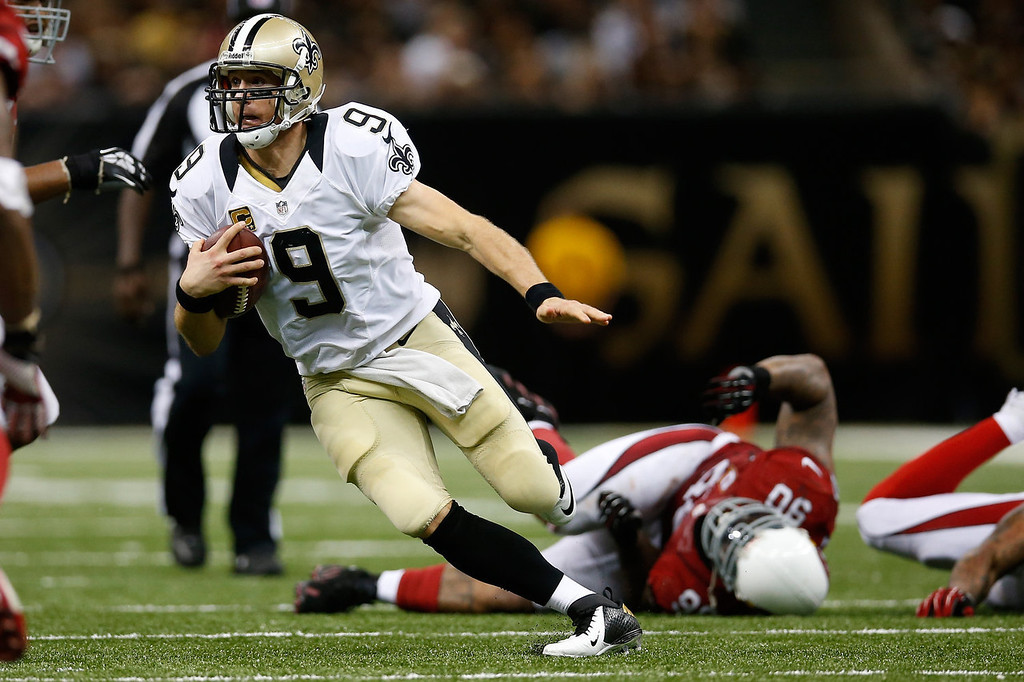 . Drew Brees #9 of the New Orleans Saints runs with the ball against the Arizona Cardinals at the Mercedes-Benz Superdome on September 22, 2013 in New Orleans, Louisiana.  (Photo by Chris Graythen/Getty Images)