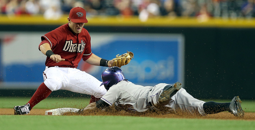 . Eric Young Jr. #1 of the Colorado Rockies safely slides into the second base under infielder Cliff Pennington #4 of the Arizona Diamondbacks on a double during the first inning of the MLB game at Chase Field on April 28, 2013 in Phoenix, Arizona.  (Photo by Christian Petersen/Getty Images)