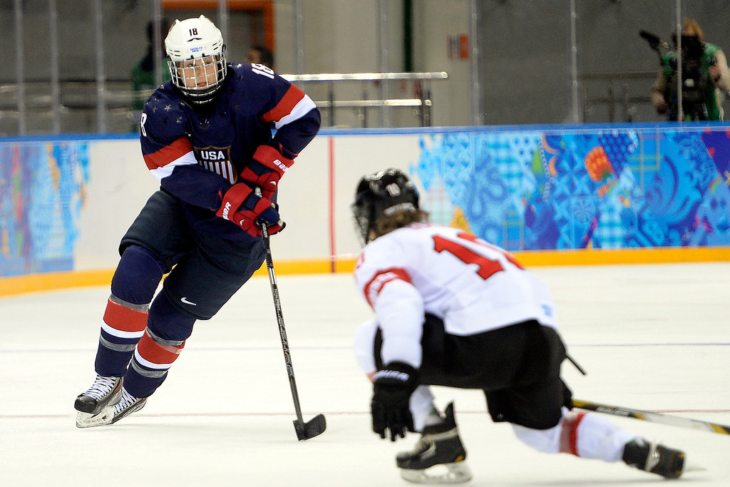 . Lyndsey Fry (18) of the U.S.A. brings the puck up the ice as Nicole Bullo (10) of the Switzerland defends during the second period of action at the Shayba Arena. Sochi 2014 Winter Olympics on Monday, February 10, 2014. (Photo by AAron Ontiveroz/The Denver Post)
