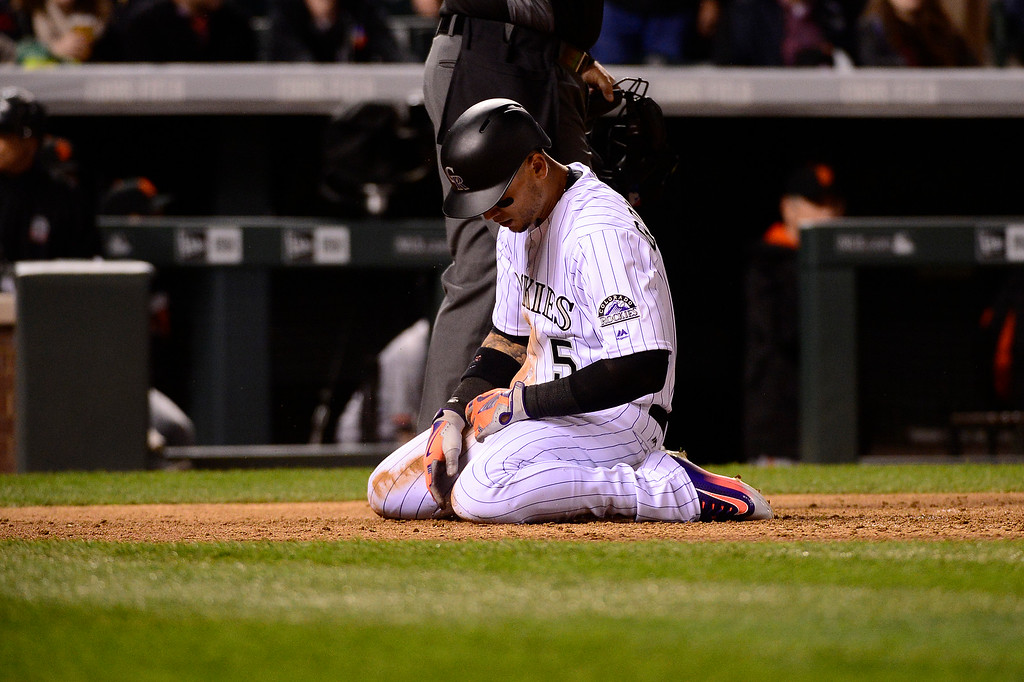 . DENVER, CO - APRIL 12: Colorado Rockies right fielder Carlos Gonzalez (5) kneels after being tagged out during the fifth inning at Coors Field on April 12, 2016 in Denver, Colorado. (Photo by Brent Lewis/The Denver Post)