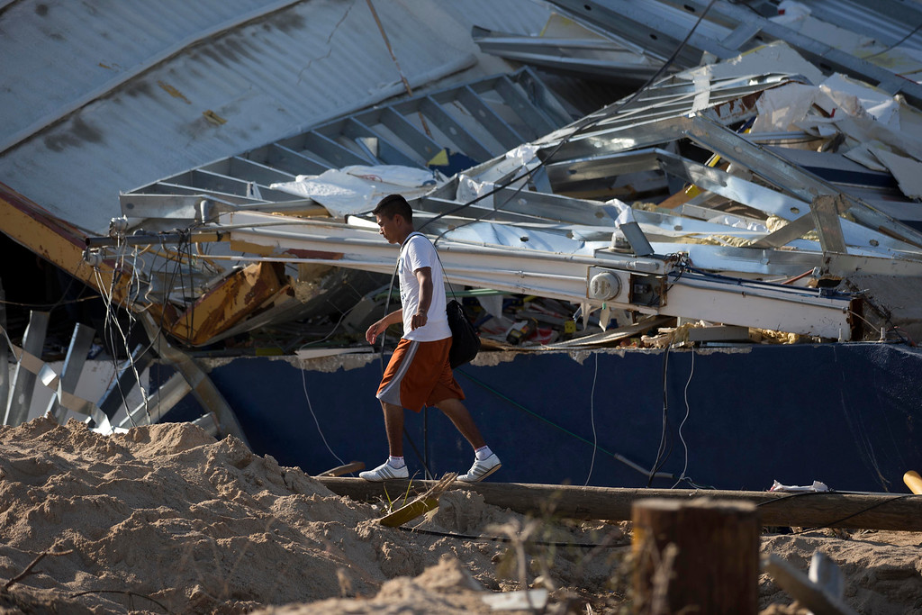 . A man walks past a destroyed building after the passing of hurricane Odile in San Jose de los Cabos, Mexico, Wednesday, Sept. 17, 2014. After Odile roared past, residents of the resort state of Baja California Sur struggled with a lack of power and running water and formed long lines for emergency supplies. There were scattered reports of looting.  (AP Photo/Dario Lopez-Mills)