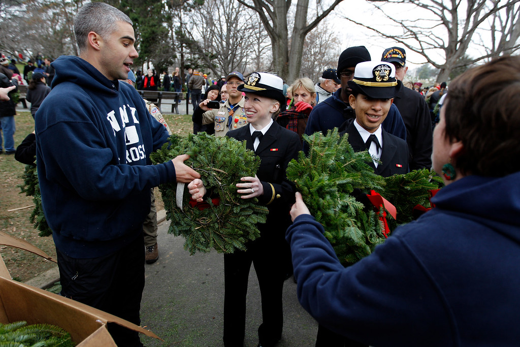 . Volunteers hand out wreaths to place at graves at Arlington National Cemetery in Arlington, Va., on Saturday Dec. 15, 2012, during Wreaths Across America Day. Wreaths Across America was started in 1992 at Arlington National Cemetery by Maine businessman Morrill Worcester and has expanded to hundreds of veterans\' cemeteries and other locations in all 50 states and beyond.  (AP Photo/Jose Luis Magana)