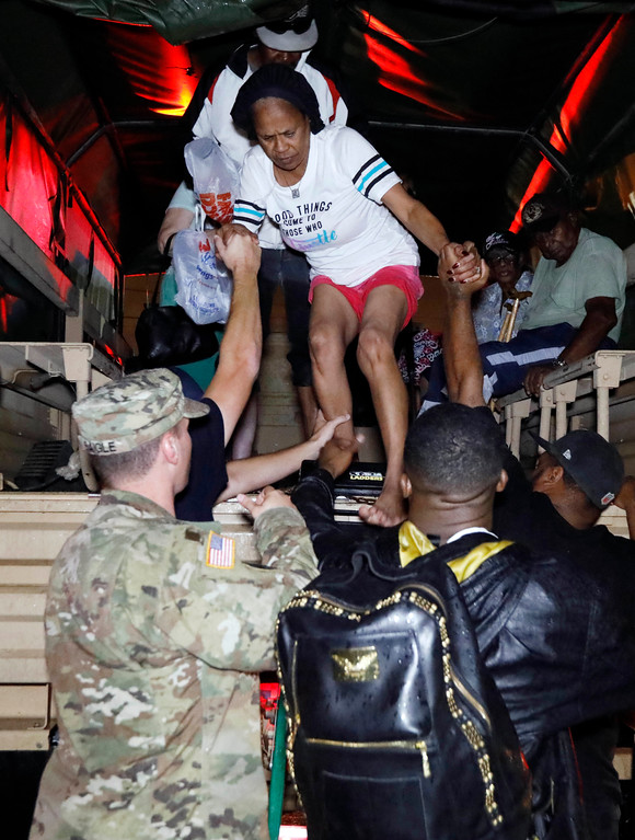 . Lake Charles rescue personnel help residents exit from the back of a vehicle late Monday night, Aug. 28, 2017, in Lake Charles, La., after flooding from Harvey\'s almost constant rain over the last two days overcame the city\'s drainage system, flooding several subdivisions and necessitating home rescues. (AP Photo/Rogelio V. Solis)