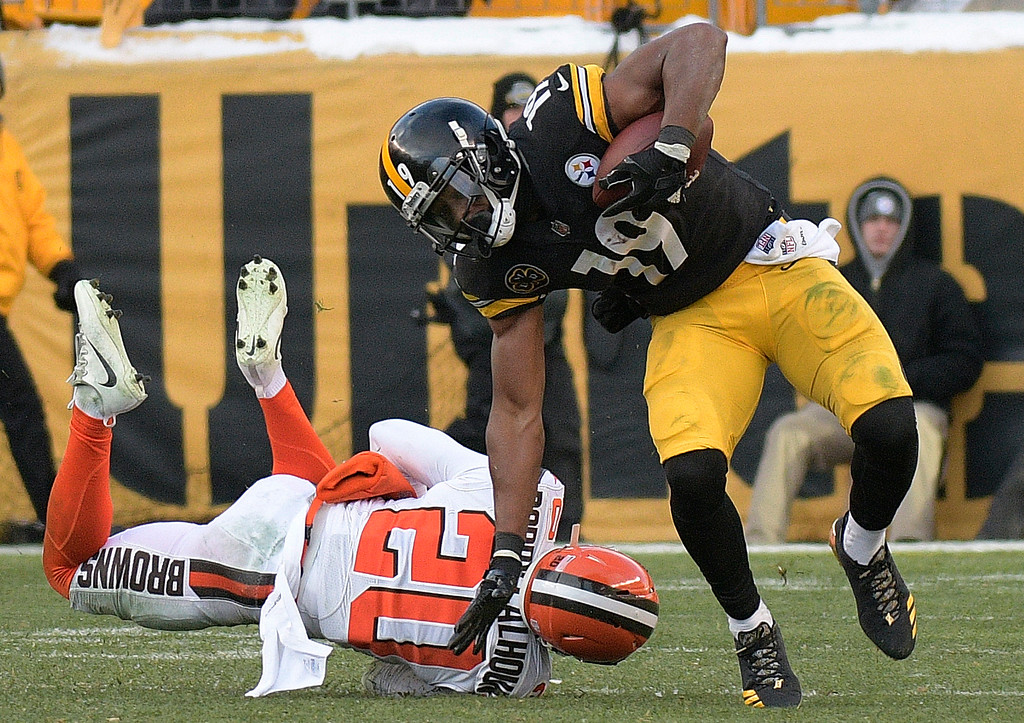 . Pittsburgh Steelers wide receiver JuJu Smith-Schuster (19) eludes a tackle by Cleveland Browns strong safety Briean Boddy-Calhoun (20) during the second half of an NFL football game in Pittsburgh, Sunday, Dec. 31, 2017. (AP Photo/Don Wright)