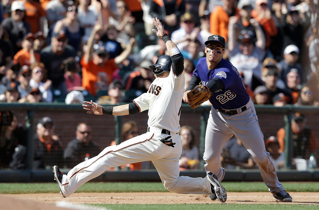 . Colorado Rockies third baseman Nolan Arenado (28) tags out San Francisco Giants\' Marco Scutaro sliding into third base during the eighth inning of a baseball game in San Francisco on May 25, 2013. (AP Photo/Jeff Chiu)