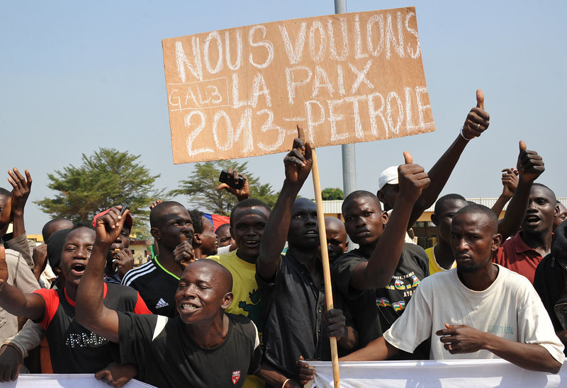 ". Demonstrators hold a placard reading ""We want peace 2013 = Petrol\"" at the airport in Bangui, as the President of the Central African Republic greets the current president of the African Union and President of Benin, on December 30, 2012. Rebels in the Central African Republic who have advanced towards the capital Bangui warned they could enter the city even as the head of the African Union prepared to launch peace negotiations. Central African President Francois Bozize also stated today he was open to a national unity government after talks with rebel leaders and that he would not run for president in 2016. SIA KAMBOU/AFP/Getty Images"