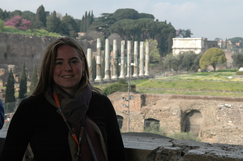 Cheryl standing in the Coliseum with Palatine Hill and the Roman Forum area in the background.