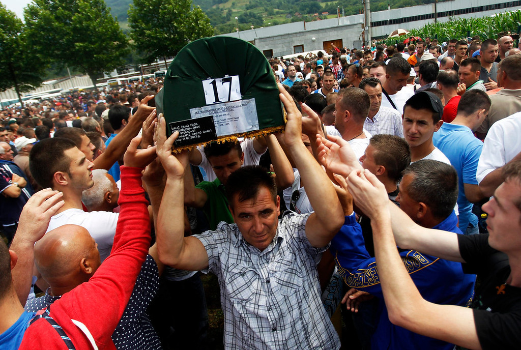 . Bosnians carry coffins of 409 newly identified victims of the 1995 Srebrenica massacre in the Potocari Memorial Center, near Srebrenica July 11, 2013. The bodies of the recently identified victims will be transported to the memorial centre in Potocari where they will be buried on July 11 marking the 18th anniversary of the massacre in which Bosnian Serb forces commanded by Ratko Mladic killed up to 8,000 Muslim men and boys and buried them in mass graves. REUTERS/Dado Ruvic