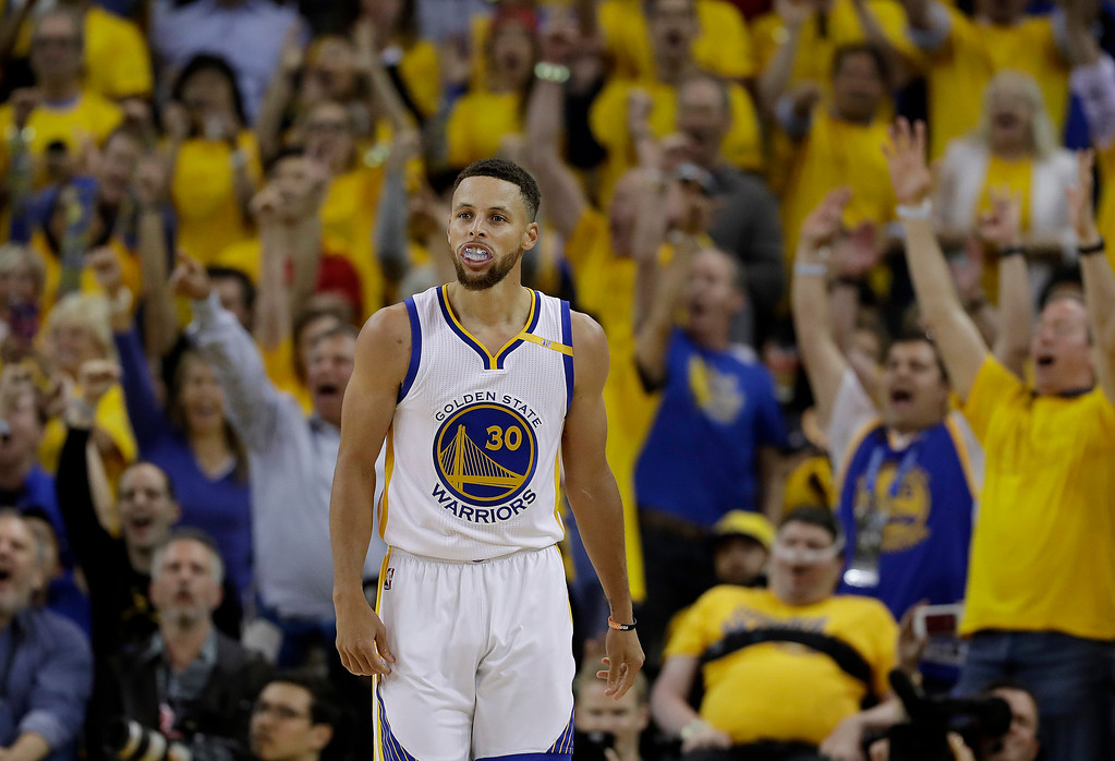 . Fans cheer after Golden State Warriors guard Stephen Curry (30) scored against the Cleveland Cavaliers during the second half of Game 1 of basketball\'s NBA Finals in Oakland, Calif., Thursday, June 1, 2017. (AP Photo/Marcio Jose Sanchez)