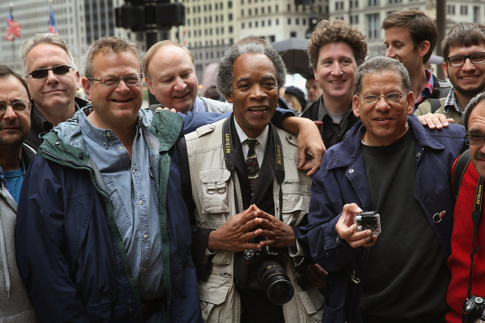 . Former Chicago Sun-Times photographers pose for a picture following a demonstration outside the offices of the Sun-Times on June 6, 2013 in Chicago, Illinois. Union members, reporters, and photographers gathered outside the newspaper\'s office to protest the company\'s decision last week to eliminate its 28-member photo staff. The newspaper chain plans to train their reporters to take pictures with iPhones to fill the void.  (Photo by Scott Olson/Getty Images)
