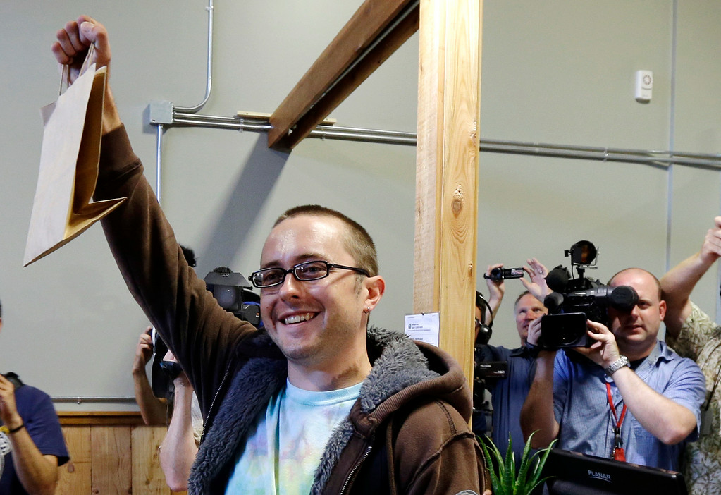 . Cale Holdsworth, of Abeline, Kan., holds up his purchase after being the first in line to buy legal recreational marijuana at Top Shelf Cannabis, Tuesday, July 8, 2014, in Bellingham, Wash. Holdsworth had been in line since 4:00 a.m. (AP Photo/Ted S. Warren)