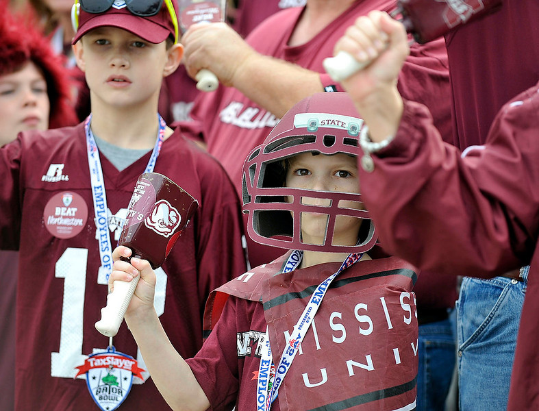 . Mississippi State fan William Braswell of Greenwood, Miss. shakes his cowbell as he greets the team as they arrive at the Gator Bowl before the start of an NCAA college football game against Northwestern, Tuesday, Jan. 1, 2013 in Jacksonville, Fla. (AP Photo/Stephen Morton)